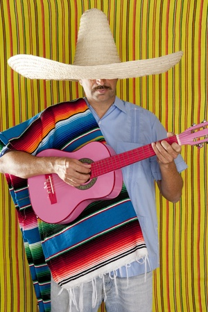 Mexican man with poncho and sombrero playing guitar typical of Mexico photo