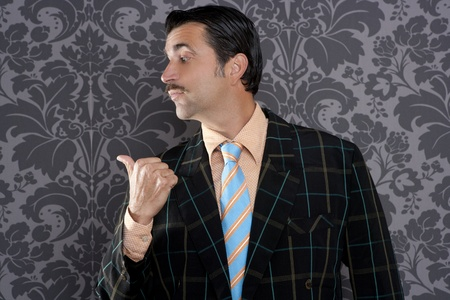 salesperson portrait pointing with thumb finger on wallpaper background photo