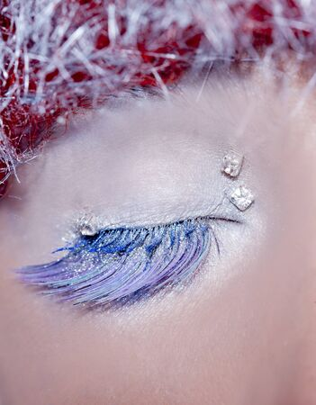 christmas winter makeup concept on closed woman eye in silver blue and red hair photo