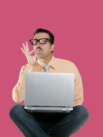 nerd man sit with laptop computer doing ok positive gesture photo