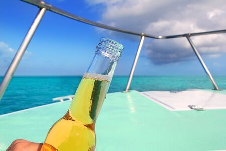 beer glass bottle on Caribbean boat bow deck sailing in turquoise sea tropical vacation photo