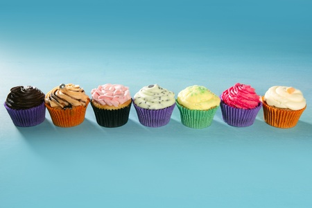 colorful cupcakes arrangement in a row on turquoise studio background photo