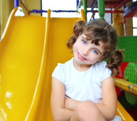 little girl posing: little girl in colorful playground sitting on yellow slide