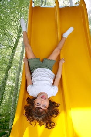 upside down: upside down little girl on playground slide laughing in forest tree park Stock Photo