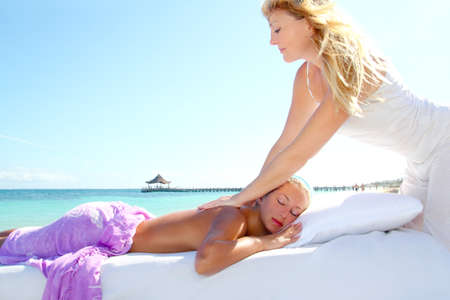 Caribbean turquoise beach with two woman doing massage therapy Stock Photo - 9942240