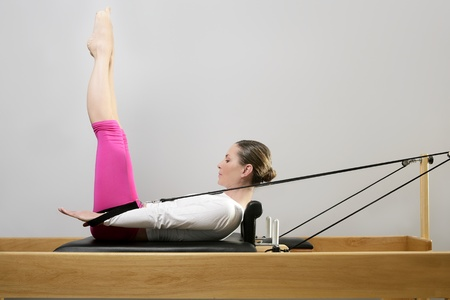 gym woman pilates instructor stretching in reformer bed photo