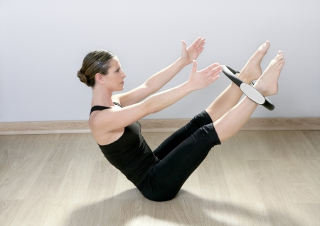 beautiful instructor woman with magic pilates ring in sport gym photo