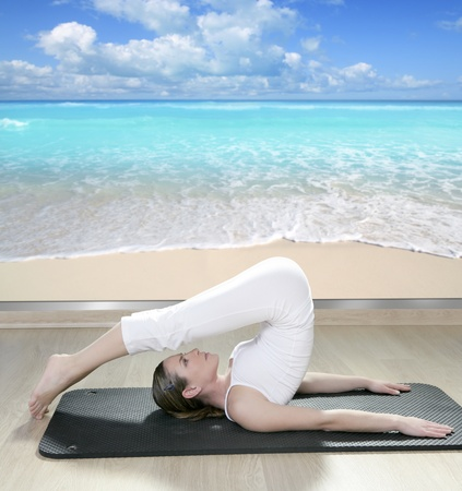 saxy: beautiful woman in black mat yoga in front a window view of tropical beach Stock Photo