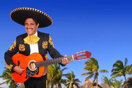 traje mexicano: Charro mexicano Mariachi tocando la guitarra en playa tropical de México