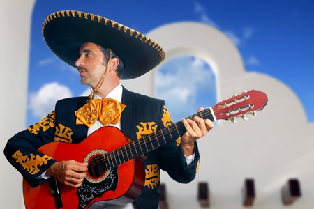 Charro Mariachi singer playing guitar in Mexico with white house background photo