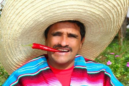 traje mexicano: Hombre mexicano con poncho y sombrero comer Aji chili rojo típico en México