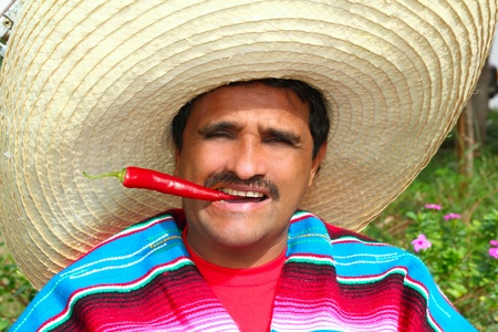 Mexican man with poncho and sombrero eating typical red chili hot pepper in Mexico photo