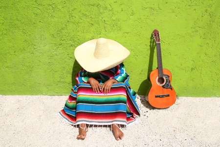 poncho: lazy typical mexican man with sombrero sitting on green wall having a nap Stock Photo