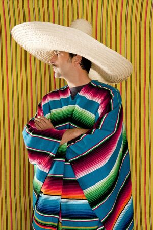 Mexican typical poncho man with sombrero and mustache over yellow background photo