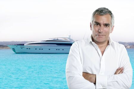miljonair senior poseren aan de voorkant een luxe jacht tijdens de zomervakantie Stockfoto