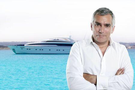 millionnaire haut posant devant un yacht de luxe pendant les vacances d'été