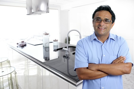 Indian latin architect man posing in front a modern house interior white kitchen photo