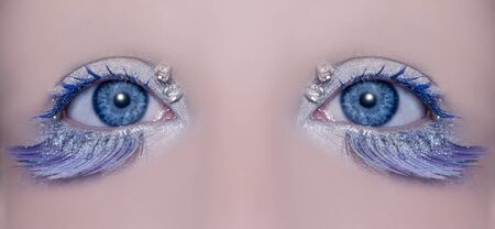 Blue eye macro closeup with a winter inspired silver makeup some jewels and feather eyelashes photo