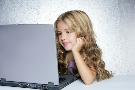 Student little school girl doing homework on laptop computer in silver background photo