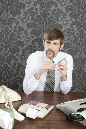 retro mustache accountant businessman sitting in office desk on vintage wallpaper photo