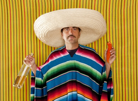 Mexican typical man eating chili hot pepper and drinking tequila with poncho photo