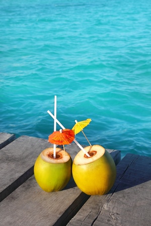 coconut coktails in caribbean on wood pier and turquoise sea photo