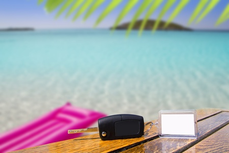 rent a car: Car rental keys on wood table with blank paper in vacation tropical beach