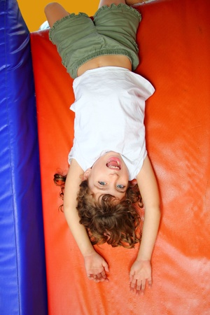 hanged: upside down little girl on playground slide laughing happy