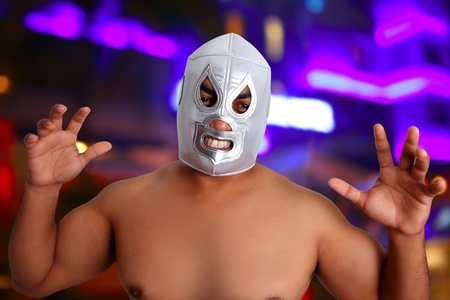aggresive: mexican wrestling mask silver fighter with aggresive gesture night blurred lights
