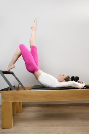 pilates teacher woman in reformer device doing legs exercise photo