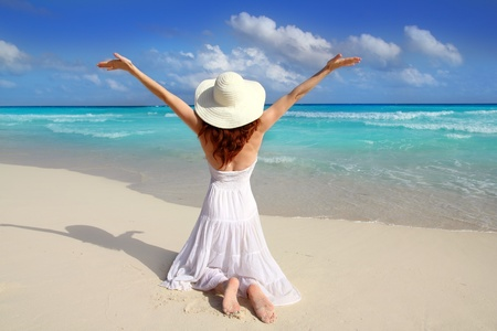 Caribbean beach woman rear view on knees happy vacation with open arms gesture photo
