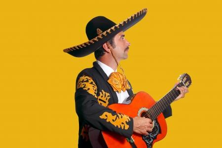 mariachi: Charro Mariachi mens het spelen gitaar op gele achtergrond
