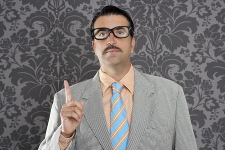 crazy man: nerd retro teacher raising finger up over vintage wallpaper background Stock Photo