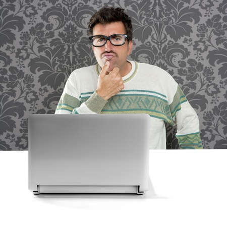 Nerd pensive man with glasses and silly expression in front a laptop computer looking for solution photo