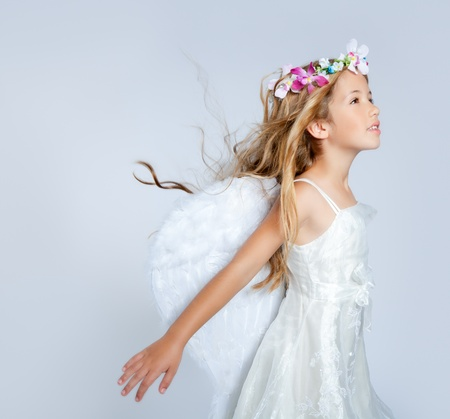 Angel children girl with wind in hair fashion white wings and flowers crown photo