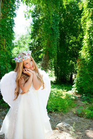 Angel children blond girl with sleeping hands gesture and fashion crown photo
