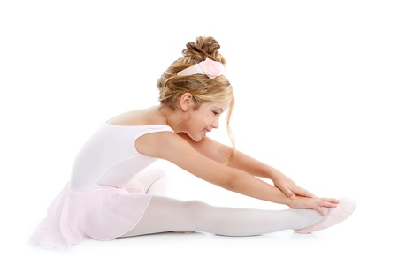 ballet: Bailarina poco bailarín de niños estiramiento sentado en el piso blanco Foto de archivo