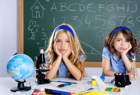 school friends: Bored student kids at school classroom in desk with blackboard