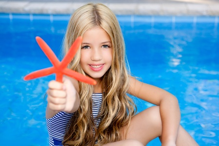 little blonde girl: children blond girl in summer vacation  pool with starfish Stock Photo