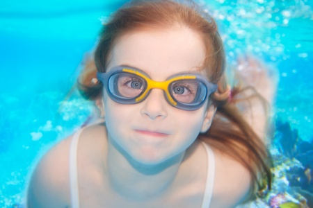 scuba goggles: children girl swimming underwater with goggles and funny gesture