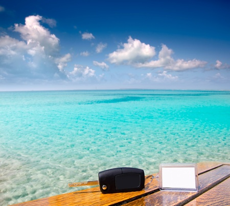 car rental: Car rental keys on wood table with blank paper in vacation Caribbean tropical beach