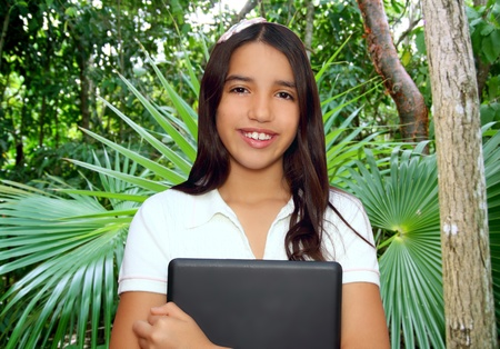 brunette teen student indian latin holding laptop in palm trees tropical jungle photo