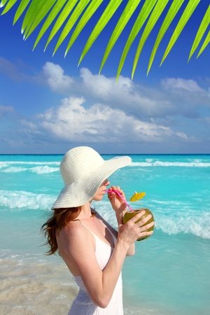 coconut drink: beach hat profile girl drinking acoconut fresh cocktail in tropical Caribbean sea