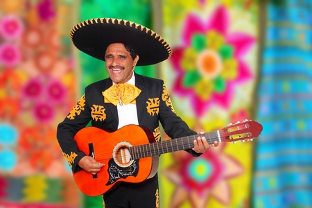 Charro Mariachi playing guitar with blurred serape background photo