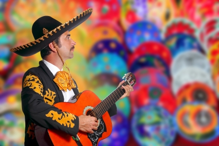 Charro Mariachi playing guitar over colorful blur handcrafts background