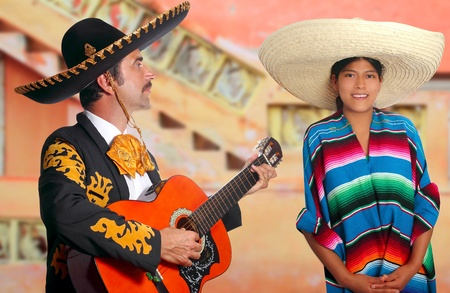 Mexican mariachi charro man singing a song to a poncho Mexico girl photo