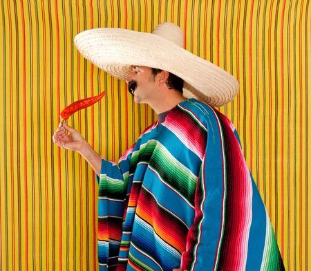 traje mexicano: Hombre mexicano típico comer ají con el poncho sobre fondo amarillo