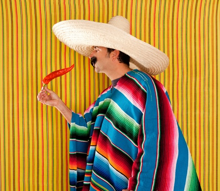serape: Mexican man eating chili hot pepper with poncho on yellow background