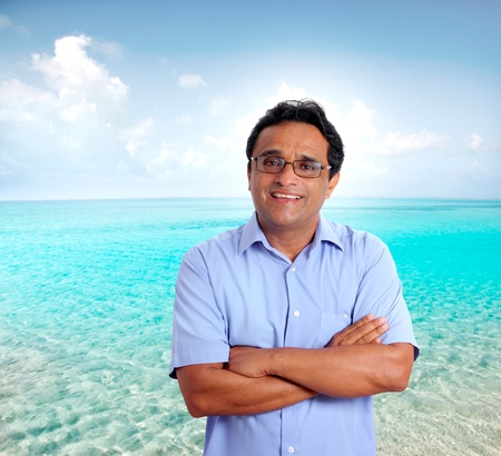 Indian latin tourist man spending his vacation in a perfect turquoise beach photo