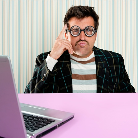 myopic: Nerd pensive man with myopic glasses and silly expression searching a solution in laptop computer